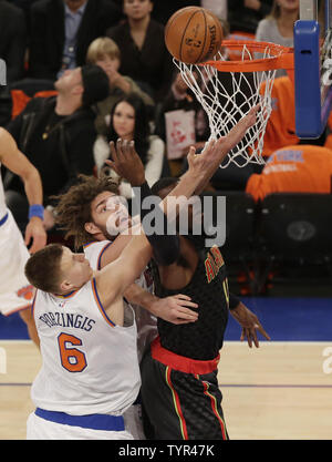New York Knicks Robin Lopez and Kristaps Porzingis defend Atlanta Hawks Paul Millsap who takes a shot under the basket at Madison Square Garden in New York City on October 29, 2015.    Photo by John Angelillo/UPI - Stock Photo