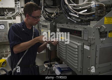 GULF (Nov. 21, 2016) Petty Officer 3rd Class Joshua Peck, assigned to the guided-missile destroyer USS Nitze (DDG 94), conducts fiber-optic data multiplexing system maintenance. Peck serves onboard Nitze as an electronics technician and is responsible for maintaining, repairing and calibrating shipboard electronic equipment. Nitze, deployed as part of the Eisenhower Carrier Strike Group, is supporting maritime security operations and theater security cooperation efforts in the U.S. 5th Fleet area of operations. - Stock Photo