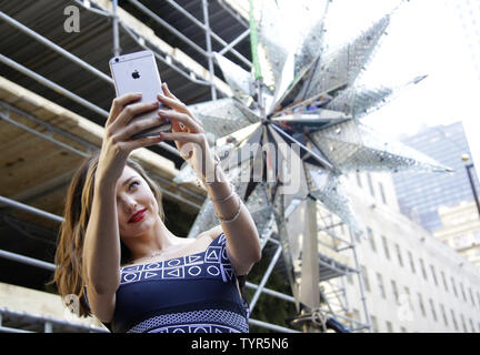 Super Model Miranda Kerr takes a selfie with the Swarovski Star before it is raised to the top of the world-famous Rockefeller Center Christmas tree on November 16, 2015 in New York City. 2015 marks the 12th year the Swarovski Star will adorn the Rockefeller Center Christmas tree. The Star is comprised of 25,000 crystals, with one million facets, and measures 9 and 1/2 feet in diameter and 1 1/2 feet deep. The Star weighs 550 pounds, including 300 pounds of crystal panels, and is composed of six outer rays and six smaller inner rays.       Photo by John Angelillo/UPI - Stock Photo