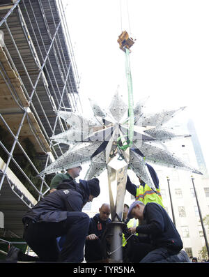 Workers help position secure The Swarovski Star before it is raised by crane to the top of the world-famous Rockefeller Center Christmas tree on November 16, 2015 in New York City. 2015 marks the 12th year the Swarovski Star will adorn the Rockefeller Center Christmas tree. The Star is comprised of 25,000 crystals, with one million facets, and measures 9 and 1/2 feet in diameter and 1 1/2 feet deep. The Star weighs 550 pounds, including 300 pounds of crystal panels, and is composed of six outer rays and six smaller inner rays.       Photo by John Angelillo/UPI - Stock Photo