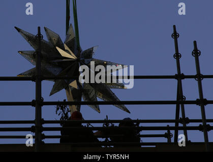 Workers help position The Swarovski Star when it is raised by crane to the top of the world-famous Rockefeller Center Christmas tree on November 16, 2015 in New York City. 2015 marks the 12th year the Swarovski Star will adorn the Rockefeller Center Christmas tree. The Star is comprised of 25,000 crystals, with one million facets, and measures 9 and 1/2 feet in diameter and 1 1/2 feet deep. The Star weighs 550 pounds, including 300 pounds of crystal panels, and is composed of six outer rays and six smaller inner rays.       Photo by John Angelillo/UPI - Stock Photo