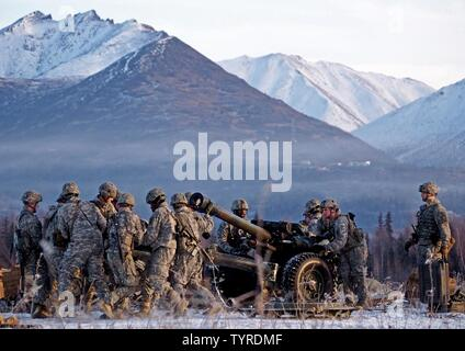Paratroopers assigned to Alpha Battery, 2nd Battalion, 377th Parachute Field Artillery Regiment, 4th Infantry Brigade Combat Team (Airborne), 25th Infantry Division, U.S. Army Alaska, prepare a M119A2 105mm howitzer for a live fire on Malemute drop zone at Joint Base Elmendorf-Richardson, Alaska, Nov. 22, 2016. USARAK is home to the Army's only Pacific airborne brigade combat team, and maintains the only airborne rapid-response capacity within the Pacific Command Area of Responsibility. - Stock Photo