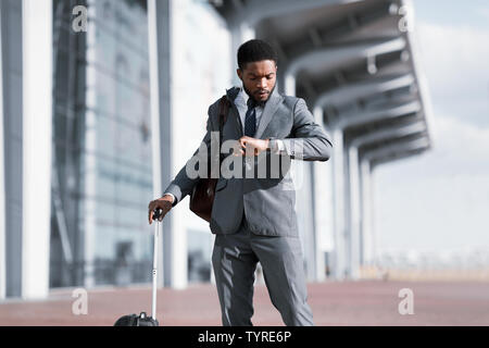 Business Traveler Checking Time On his Wristwatch At Airport - Stock Photo