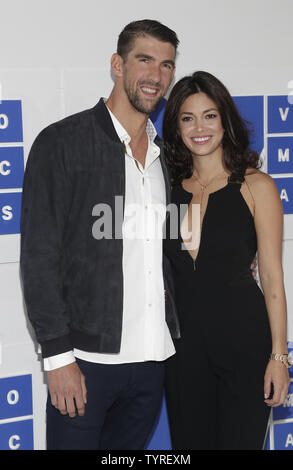 Michael Phelps and Nicole Johnson arrive on the red carpet with a view of the Empire State Building at the 2016 MTV Video Music Awards at Madison Square Garden in New York City on August 28, 2016. Performers at the 2016 MTV VMA's include Rihanna, Britney Spears, Ariana Grande and Nicki Minaj.       Photo by John Angelillo/UPI - Stock Photo