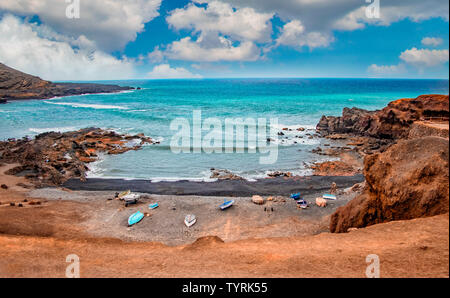 The black volcanic beach with sea bay. The water is turqoise and clear and blue sky in the background, El Golfo, Lanzarote, Canary islands, Spain. - Stock Photo