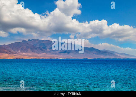 View of the hill on the island Fuerteventura near Morro Jable, Canary islands, Spain. There is clear blue water and beautiful sky.