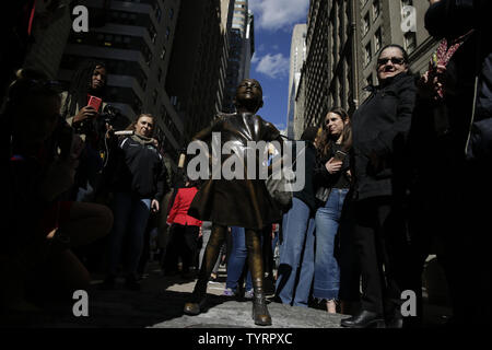 People gather and take photos of a bronze statue of a defiant girl in front of Wall Street's iconic charging bull statue on International Women's Day in New York City on March 8, 2017.  Installed by State Street Global Advisors, a branch of Boston-based State Street Corp., the 'Fearless Girl' statue was placed in the financial heart of NYC as a call for more women to serve on corporate boards. The work is by artist Kristen Visbal, a Lewes, Del., artist who has created many bronze sculptures.    Photo by John Angelillo/UPI - Stock Photo