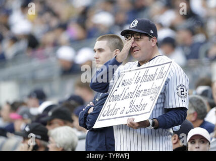 Fans hold up signs and wear shirts honoring Derek Jeter at a ceremony retiring his number before the Houston Astros play the New York Yankees at Yankee Stadium in New York City on May 14, 2017. The New York Yankees former shortstop had his No. 2 retired and was also honored with a plaque in Monument Park.     Photo by John Angelillo/UPI - Stock Photo