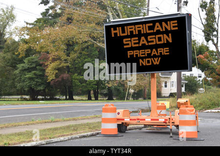 Digital electronic mobile road sign that says Hurricane Season prepare now, on the side of a tree lined neighborhood road - Stock Photo