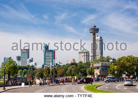 NIAGARA FALLS, CANADA - AUGUST 27, 2017: Crowds of tourists walk along the Niagara Parkway with the city in the background. - Stock Photo
