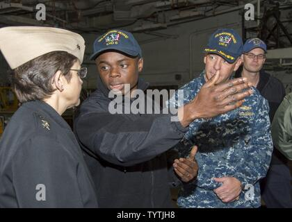 SASEBO, Japan (Nov. 29, 2016) Petty Officer 2nd Class Dominic Mando (center), well deck assistant leading petty officer, describes the amphibious capabilities of Bonhomme Richard to Chief of Chaplains Rear Adm. Margaret Kibben in the well deck of amphibious assault ship USS Bonhomme Richard (LHD 6).  Bonhomme Richard, forward-deployed to Sasebo, Japan, is serving forward to provide a rapid-response capability in the event of a regional contingency or natural disaster. - Stock Photo