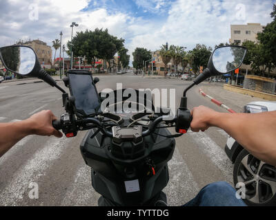 Tel Aviv, Israel - April 16, 2019: Riding a scooter in the busy urban streets during a cloudy and sunny day. - Stock Photo