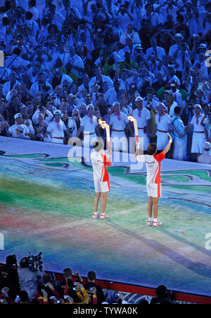 Two runners hold the Olympic Torches and face the crowd of athletes as the flame makes its way around China's National Stadium during the opening ceremonies of the 2008 Summer Olympics in Beijing, China on August 8, 2008.     (UPI Photo/Mike Theiler) - Stock Photo