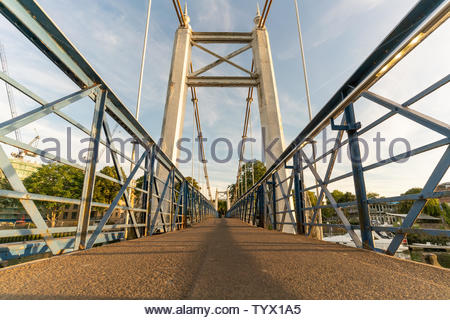 man walking over foot bridge in evening Evening at teddington Lock - Stock Photo
