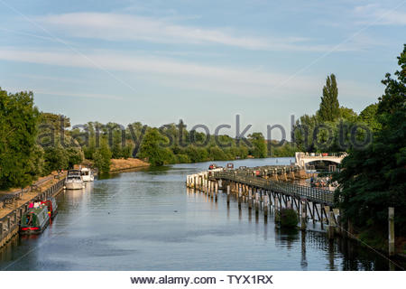 Boats moored on the docks along the river Thames in Teddington West London early evening as the sun is starting to set. - Stock Photo