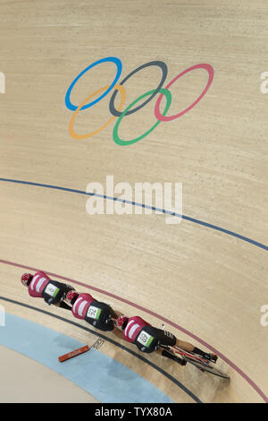 Cyclists from the Denmark team speed past the Olympic ring symbol during the Men's Team Pursuit Qualifying round at the Rio Olympic Velodrome during the 2016 Summer Olympics in Rio de Janeiro, Brazil, on August 11, 2016. Denmark qualified for the next round with a time of 3:55.396.   Photo by Richard Ellis/UPI.. - Stock Photo