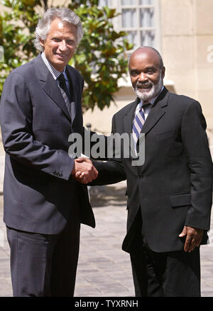 French Prime Minister Dominique de Villepin (L) greets visiting Haitian President Rene Preval upon his arrival at the Matignon Hotel in Paris, June 29, 2006. Prevel said this week that Haiti can't expect to be seen as a desirable tourist destination until necessary roads are built and political stability is achieved. (UPI Photo/Eco Clement) - Stock Photo