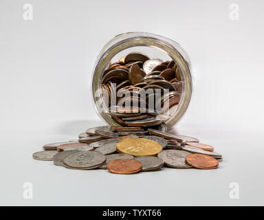 Spare change jar laying on its side with coins spilling out - Stock Photo
