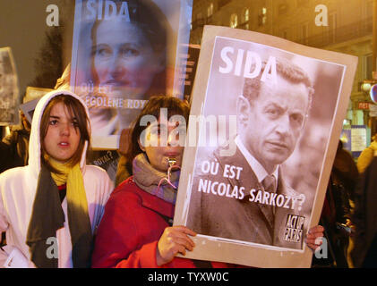 Activists hold placards with portraits of rival presidential candidates, Segolene Royal (L) and Nicolas Sarkozy (R) during a demonstration in Paris on November 30, 2006, on the eve of World Aids Day. (UPI Photo/Eco Clement) - Stock Photo