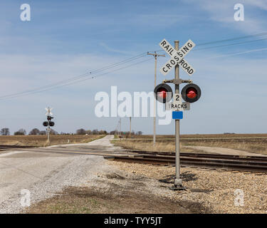 Railroad crossing with warning sign and warning lights on a rural road in the countryside - Stock Photo