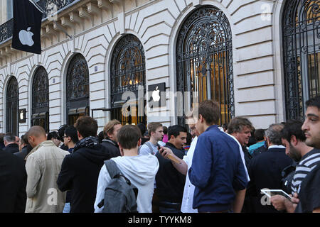 Customers line up in front of the Apple Store near Place de l'Opera before the release of the next generation iPhone 6 models today in Paris on September 19, 2014.  The iPhone 6 and the larger iPhone 6 Plus feature improved camera autofocus, increased storage capacity, and NFC Apple Pay mobile wallet.   UPI/David Silpa - Stock Photo