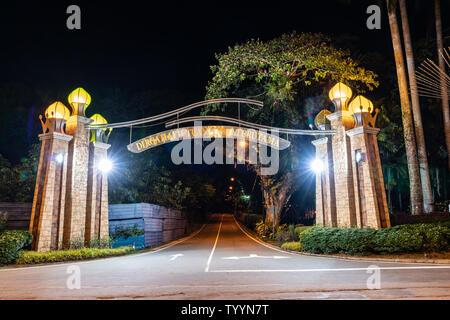 KOTA KINABALU BORNEO - MAY 30 2019; Entrance arch across street illuminated at night. - Stock Photo