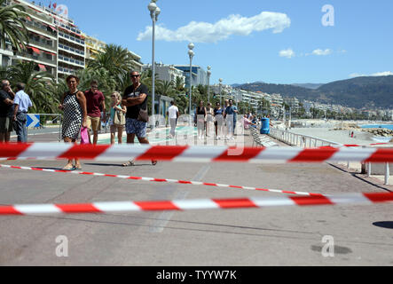People walk along the Promenade des Anglais still open to pedestrians in Nice, Southern France, on July 17, 2016. More than 80 people were killed and many more injured when a truck mowed down a crowd of revelers attending the Bastille Day fireworks. Photo by Maya Vidon-White/UPI - Stock Photo