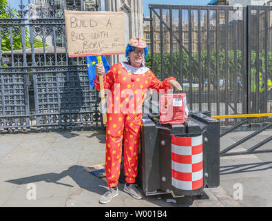 London / UK - June 26th 2019 - Pro-EU anti-Brexit protester dressed as a clown and holding a sign saying 'Build a bus with Boris workshop RRP £350mil' - Stock Photo
