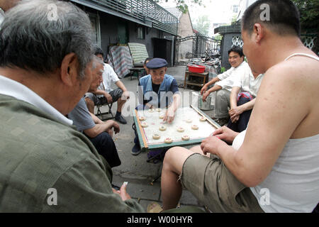 Chinese men play checkers outside in an old neighborhood in Beijing, China on June 20, 2008.  (UPI Photo/Stephen Shaver) - Stock Photo