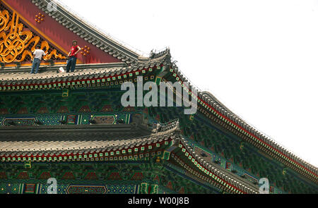 Two men adjust and repair the lighting on the roof of the Hong Kong Jockey Club's new clubhouse, just weeks before the start of the 2008 Beijing Olympic Games, in Beijing July 23, 2008.  (UPI Photo/Stephen Shaver) - Stock Photo