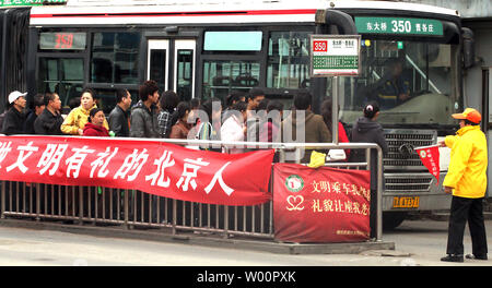 Chinese commuters stand in line to board an arriving bus in downtown Beijing on April 30, 2010.  Chinese Premier Wen Jiabao last week calld for greater efforts to fulfill the energy-aving and emission reduction goals set out in the nation's 11th Five Year Plan.  According to the plan laid out in 2006, China will cut its per unit GDP energy consumption by 20 percent compared with 2005 levels by the end of this year.    UPI/Stephen Shaver - Stock Photo