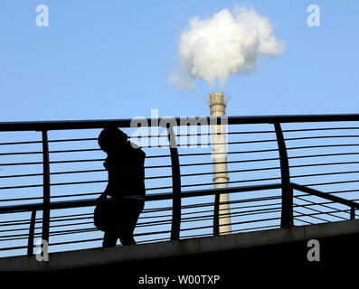 Chinese pedestrians walk past Beijing's downtown, coal-powered energy plant as record low temperatures hit the capital December 16, 2010. China could face power and energy shortages this winter as supplies of oil and coal will be hit hard by the country's aggressive urbanization, according to China's top economic planning body.    UPI/Stephen Shaver - Stock Photo