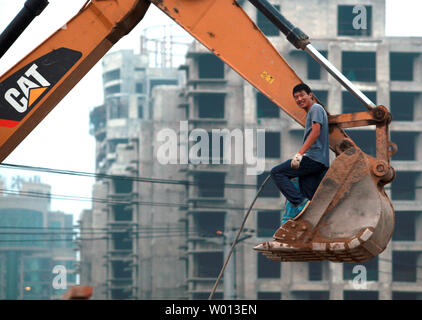 A Chinese worker stands in an elevated shovel of a CAT