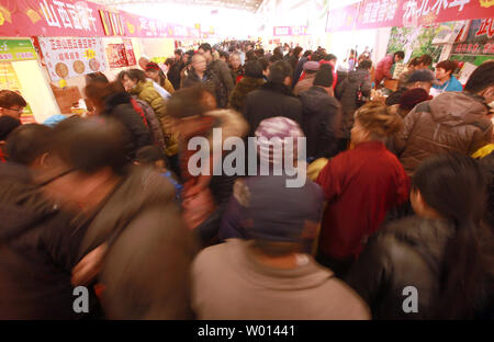 Chinese shop for traditional holiday food on sale at a market ahead of China's Lunar New Year, also known as the Spring Festival and the country's main national holiday, in Beijing on January 26, 2014. Chinese are hugely symbolic when it comes to celebrating national holidays, with the Spring Festival akin to Thanksgiving when it comes to eating mass quantities of food with family and friends.  But with rising food prices and inflation, it is predicted this year will see a sharp decline in lavish banquets and overall food purchases.     UPI/Stephen Shaver..Rising food prices may be ChinaÕs big - Stock Photo