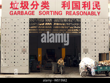 Chinese garbage collectors deliver both commercial and residential trash to a recycling garbage depot in Beijing on November 29, 2015.  China's major cities have aggressively encouraged the recycling of plastics, paper and aluminum trash due to the enormous amount of waste being produced nationwide.     Photo by Stephen Shaver/UPI - Stock Photo