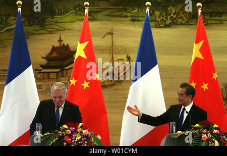French Foreign Minister Jean-Marc Ayrault (L) holds a joint  press conference with his Chinese counterpart Wang Yi in Beijing on April 14, 2017.   China and France recently signed agreements on nuclear energy and science cooperation in agriculture and medicine.      Photo by Stephen Shaver/UPI - Stock Photo