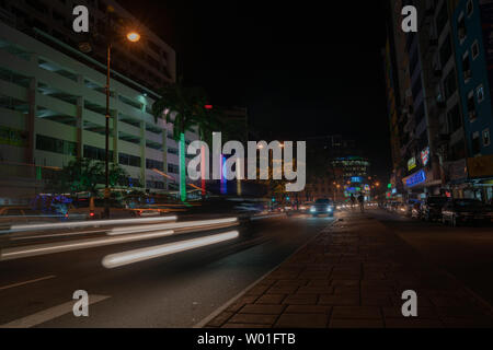 KOTA KINABALU BORNEO - MAY 30 2019; Street scene with neon lights and light trails from moving cars in long exposure - Stock Photo