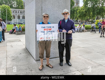 London / UK - June 26th 2019 - Couple carry a Time Is Now sign in parliament square, as part of a Time Is Now climate coalition event - Stock Photo