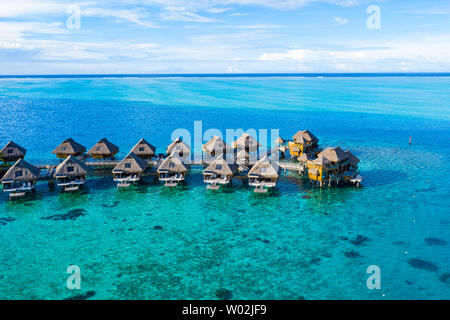 Travel vacation paradise aerial drone video with overwater bungalows in coral reef lagoon sea. Aerial video from Bora Bora, French Polynesia, Tahiti, South Pacific Ocean. - Stock Photo