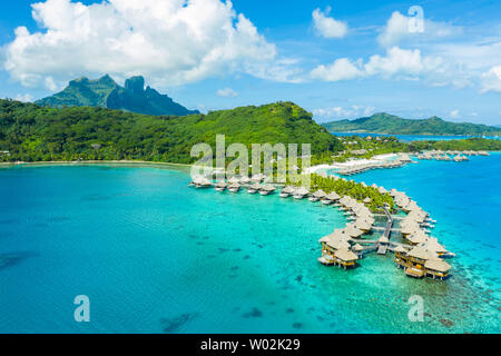 Travel vacation paradise aerial drone video with overwater bungalows luxury resort in coral reef lagoon ocean beach. Aerial of Mount Otemanu, Bora Bora, French Polynesia, Tahiti, South Pacific Ocean