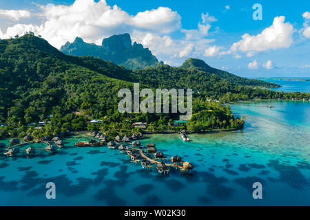 Bora Bora aerial drone video of travel vacation paradise with overwater bungalows luxury resort, coral reef lagoon ocean beach. Mount Otemanu, Bora Bora, French Polynesia, Tahiti, South Pacific Ocean - Stock Photo