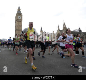 Fun Runners pass Big Ben as they take part in the 35th 2016 Virgin London Marathon in London on April 24, 2016. Photo by Hugo Philpott/UPI - Stock Photo