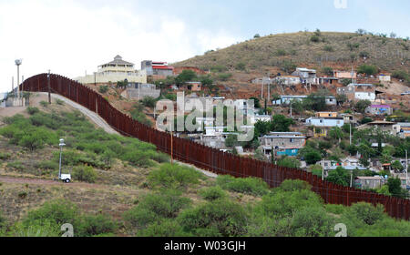 The border fence stretches for miles between the United States and Mexico near Nogales, Arizona on July 13, 2014.  More than 57,000 children from Central America have crossed the U.S. border alone since October 1, 2013.  President Obama has asked congress for $3.7 million to deal with the influx.    UPI/Art Foxall - Stock Photo
