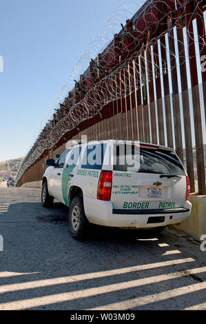 A United States Border Patrol vehicle sits in the shadow of the border fence now adorned with barbed wire heading East along the United States-Mexico border in Nogales, Arizona on February 8, 2019. The Arizona city has ordered Federal Officials to remove the barbed wire.  Photo by Art Foxall/UPI - Stock Photo
