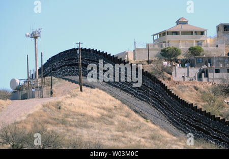 Surveillance cameras and barbed wire sit along the U.S. side of the border fence with Mexico, shown here, heading East from Nogales, Arizona on February 8, 2019. The Arizona city has ordered Federal Officials to remove the barbed wire. Photo by Art Foxall/UPI - Stock Photo