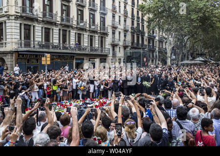 People take photos as Spain's King Felipe and Queen Letizia paying respect at a memorial tribute of flowers, messages and candles to the van attack victims in Las Ramblas promenade, Barcelona, Spain, on August 19, 2017, two days after a van ploughed into the crowd, killing 14 persons and injuring over 100. Drivers have plowed on August 17, 2017 into pedestrians in two quick-succession, separate attacks in Barcelona and another popular Spanish seaside city, leaving 14 people dead and injuring more than 100 others. photo by Angel Garcia/ UPI - Stock Photo