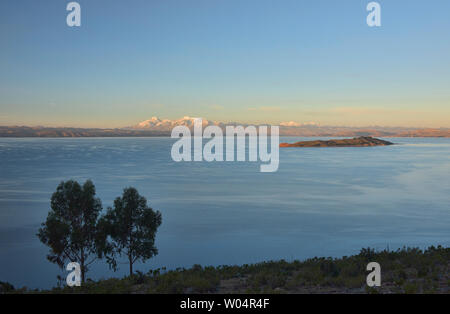 View of the entire Cordillera Real and Isla de la Luna at sunset across Lake Titicaca, Isla del Sol, Bolivia - Stock Photo