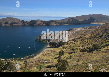 Boats in the bay and agricultural terracing on Isla del Sol, Lake Titicaca, Bolivia - Stock Photo