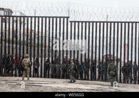 Border Patrol agents stand in front of the border fence that divides the United States and Mexico at Border Field State Park in San Diego, California on December 10, 2018.     Photo by Ariana Drehsler/UPI - Stock Photo