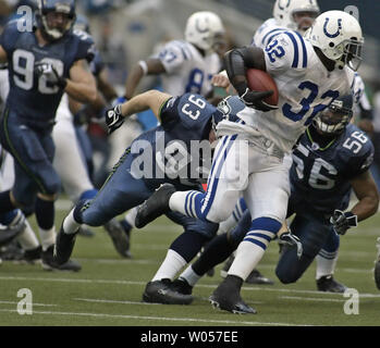 Indianapolis Colts running back Edgerrin James (32) tries to turn the corner against Seattle Seahawk defenders Craig Terrill (93) and Leroy Hill (56)  in Seattle December 24, 2005. James rushed for 14 yards in the Colts 13-24 loss to the Seahawks. (UPI Photo/Jim Bryant) - Stock Photo